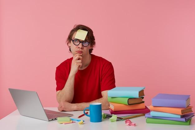 Jonge denkende man met bril draagt in rood t-shirt, met een sticker op zijn voorhoofd, zit bij de tafel en werkt met notitieboekje en boeken, kijkt omhoog en raakt kin, geïsoleerd op roze achtergrond.