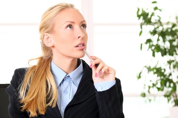Jonge denkende zakenvrouw in het kantoor