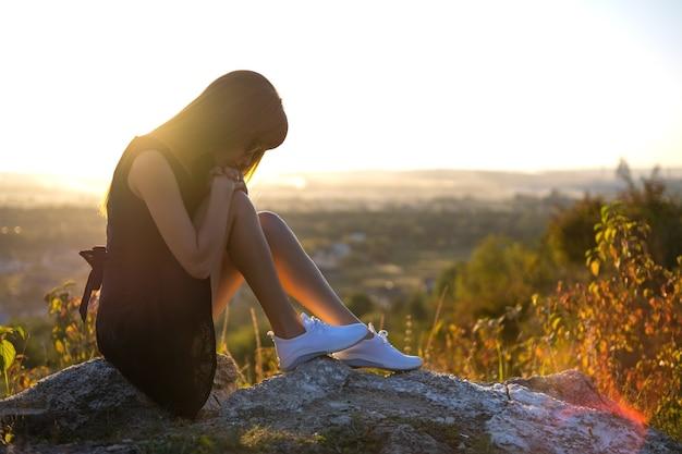 Jonge depressieve vrouw in zwarte korte zomerjurk zittend op een rots buiten denkend bij zonsondergang. modieuze vrouw overweegt in warme avond in de natuur.
