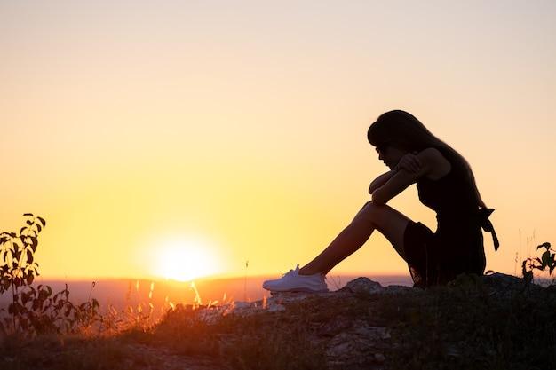 Jonge depressieve vrouw in zwarte korte zomerjurk zittend op een rots buiten denkend bij zonsondergang.