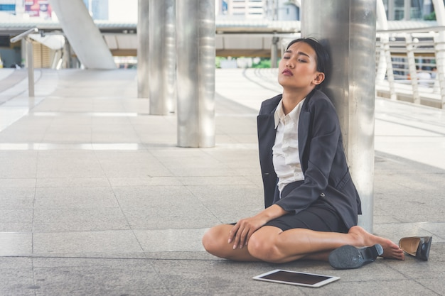 Jonge depressieve zakenvrouw zittend op de vloer
