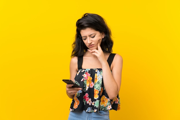 Jonge die vrouw op geel wordt geïsoleerd die mobiele telefoon met behulp van