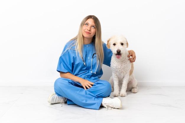 Jonge dierenarts vrouw met hond zittend op de vloer en opzoeken