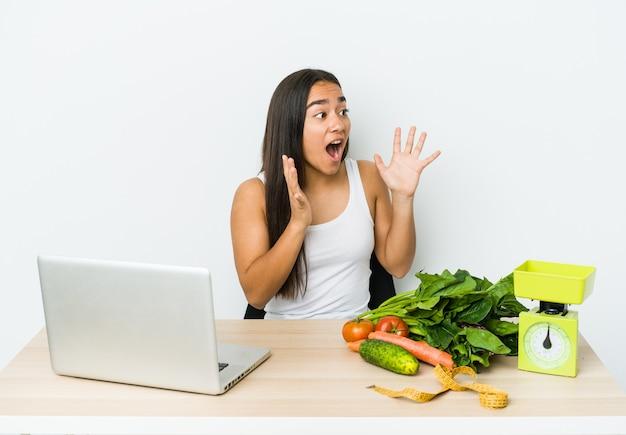 Jonge diëtist aziatische vrouw geïsoleerd op een witte muur schreeuwt luid, houdt ogen open en handen gespannen