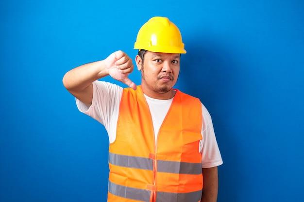 Jonge dikke aziatische bouwvakker met een oranje veiligheidsvest en helm die er ongelukkig uitziet