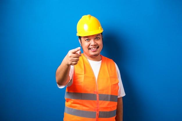 Jonge dikke aziatische bouwvakker met een veiligheidshelm die met de vinger wijst