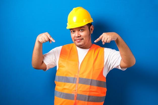 Jonge dikke aziatische man over een blauwe achtergrond met een aannemersuniform en een veiligheidshelm wijzend
