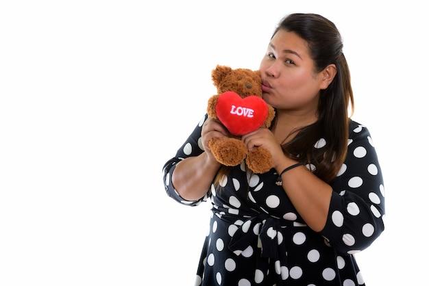 Jonge dikke aziatische vrouw bedrijf en kussen teddybeer