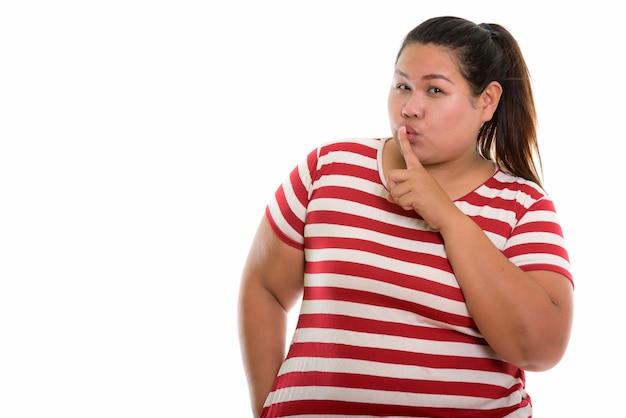 Jonge dikke aziatische vrouw met vinger op lippen