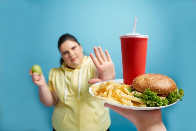 Jonge dikke mooie brunette vrouw in gele trui verse groene appel in de ene hand houden en door een andere hand laten zien dat ze weigert om fastfood op witte plaat te eten. concept van gewichtsverlies