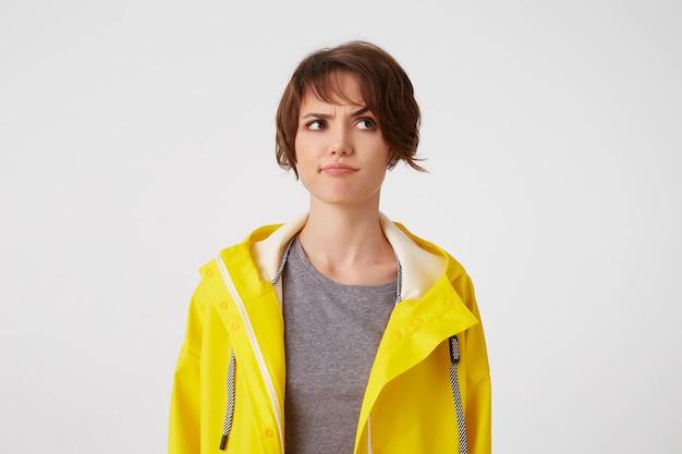 Jonge dobting kortharige vrouw in geelregenjas, fronsend kijkt weg, staat op een witte achtergrond, kijkt ontevreden en twijfelend.