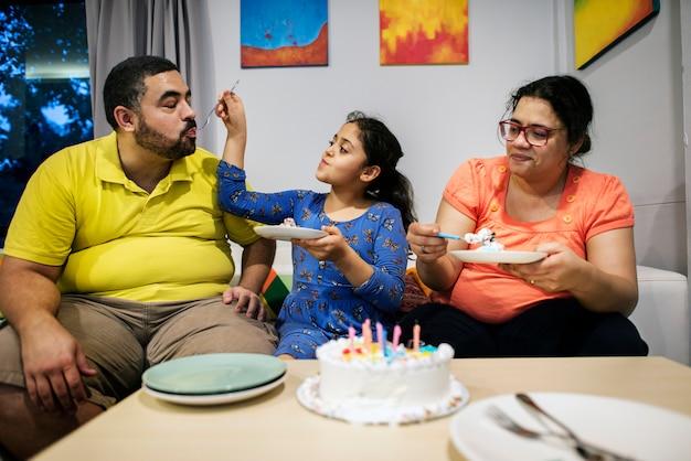 Jonge dochter die haar vader met cake voedt