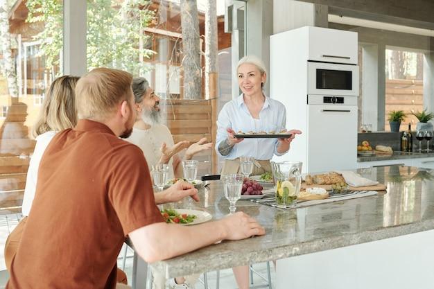 Jonge dochter en zoon helpen oudere ouders om de tafel te dienen voor het familiediner in het landhuis