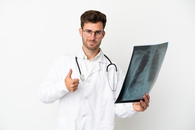 Jonge dokter blanke man over geïsoleerd op een witte achtergrond, gekleed in een doktersjas en met een botscan