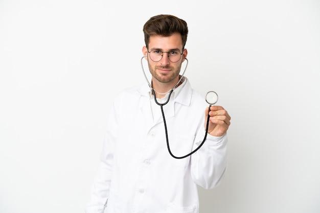 Jonge dokter blanke man over geïsoleerd op een witte achtergrond, gekleed in een doktersjurk en met stethoscope
