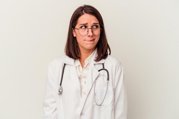 Jonge dokter blanke vrouw geïsoleerd op een witte achtergrond verward, voelt zich twijfelachtig en onzeker.