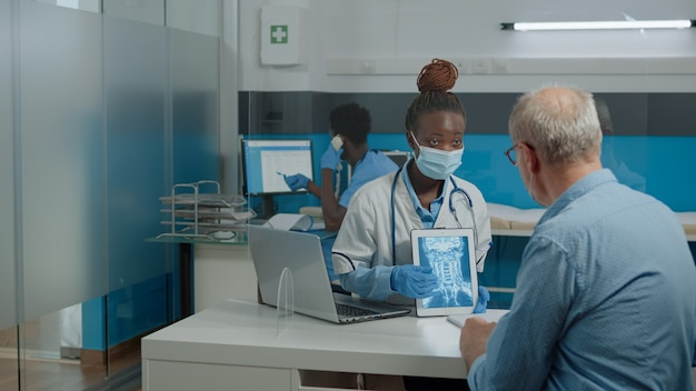 Jonge dokter die röntgenfoto's analyseert op digitale tablet