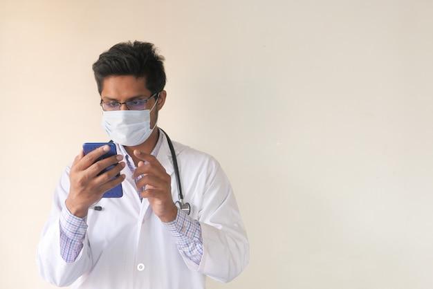 Jonge dokter in gezichtsmasker met behulp van slimme telefoon binnen