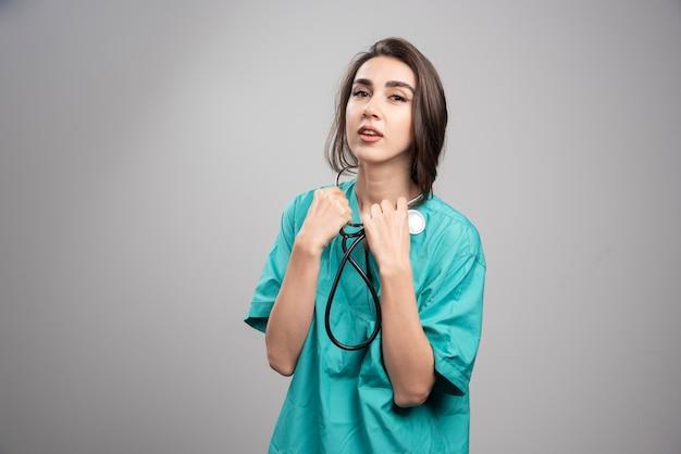 Jonge dokter in uniform met behulp van stethoscoop op grijze muur.