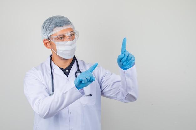 Jonge dokter in witte jas, muts, handschoenen punten met beide handen vingers