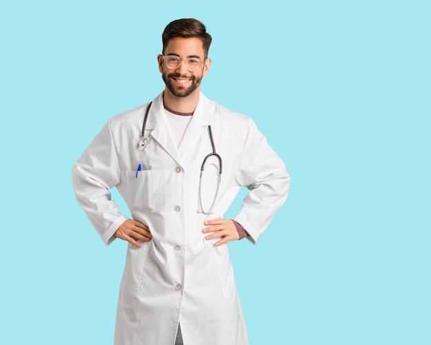 Jonge dokter man met de handen op de heupen