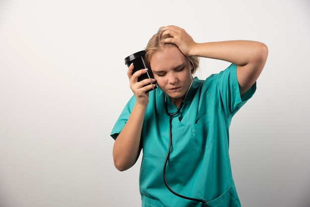 Jonge dokter met koffie met hoofdpijn op wit.