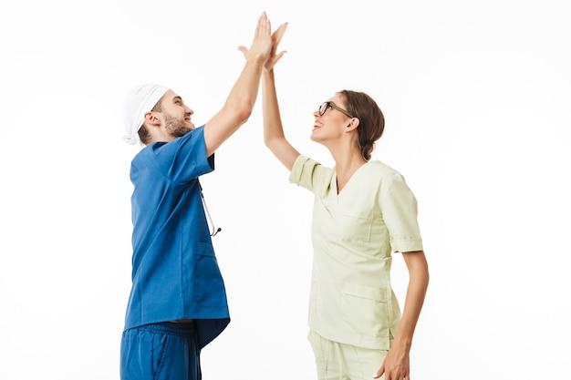 Jonge dokter met phonendoscope op nek en lachende verpleegster in brillen en uniform met vreugde vijf gebaar aan elkaar geven