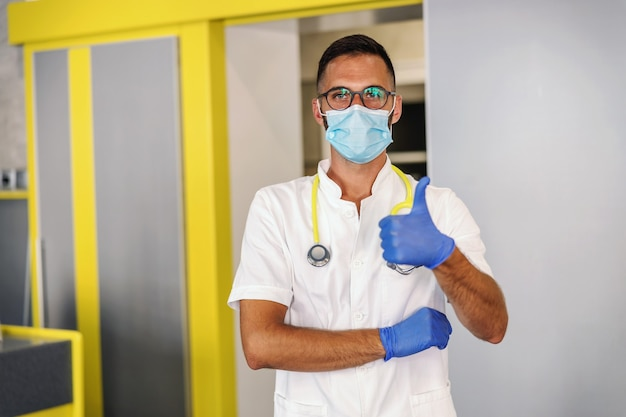 Jonge dokter met rubberen handschoenen, beschermend masker en in steriele witte uniforme staande in het ziekenhuis en duimen opdagen.