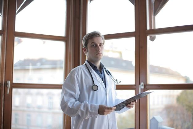 Jonge dokter permanent in zijn kantoor met ramen op de achtergrond