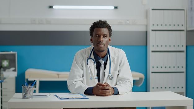 Jonge dokter praat over videogesprek met patiënt voor online consult op afstand terwijl hij aan het bureau in de kast zit. medic die internetcommunicatie gebruikt voor telegeneeskundebehandeling