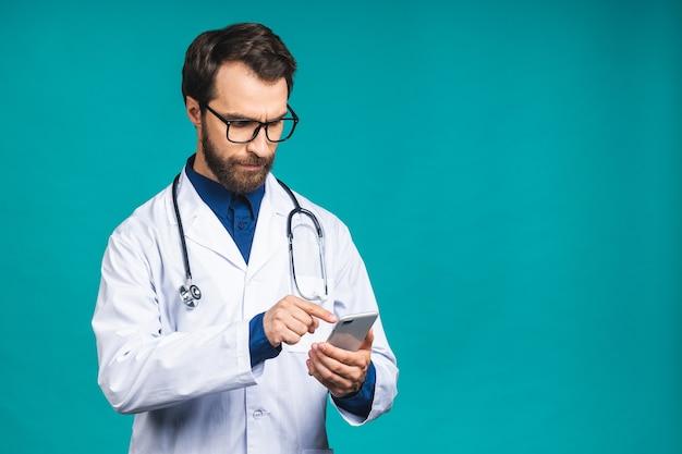 Jonge dokter sms't op een slimme telefoon geïsoleerd op een blauwe achtergrond. mobiele telefoon gebruiken.