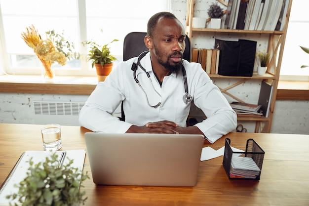 Jonge dokter tijdens zijn werk met patiënten op kantoor