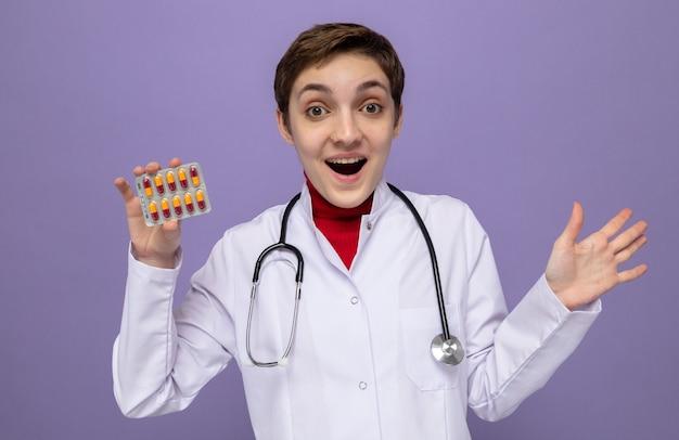 Jonge doktersmeisje in witte jas met stethoscoop om nek met blaar met pillen blij en opgewonden met opgeheven arm op paars