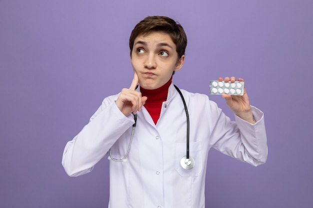 Jonge doktersmeisje in witte jas met stethoscoop om nek met blaar met pillen en verbaasd opkijkend over paarse muur