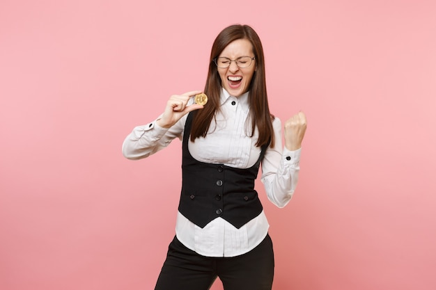Jonge dolblij mooie zakenvrouw in glazen met bitcoin doen winnaar gebaar geïsoleerd op pastel roze achtergrond. dame baas. prestatie carrière rijkdom concept. kopieer ruimte voor advertentie.