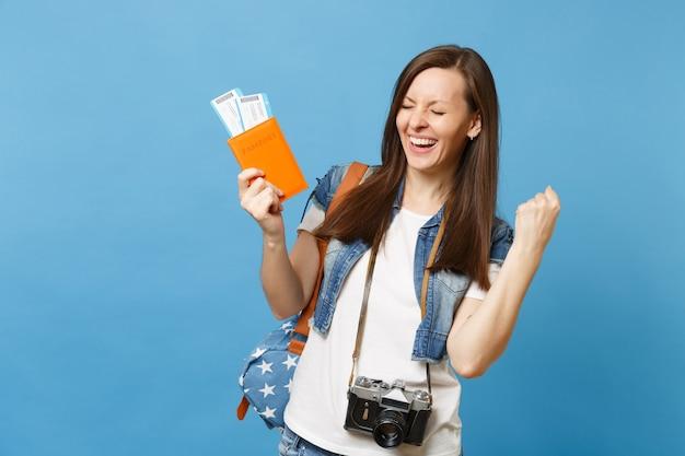 Jonge dolblij studente met retro vintage fotocamera met paspoort, instapkaart tickets doen winnaar gebaar geïsoleerd op blauwe achtergrond. onderwijs op de universiteit in het buitenland. vliegreis vlucht.