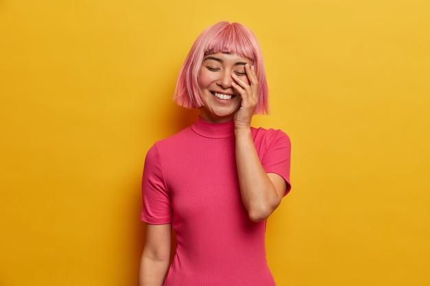 Jonge dolblij vrouw lacht vrolijk, maakt gezicht palm, sluit eues van gelach, vertoont witte tanden, heeft roze haar