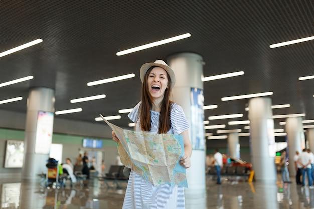 Jonge dolblije reizigerstoeristenvrouw in hoed die papieren kaart vasthoudt, route zoekt en wacht in de lobbyhal op de internationale luchthaven
