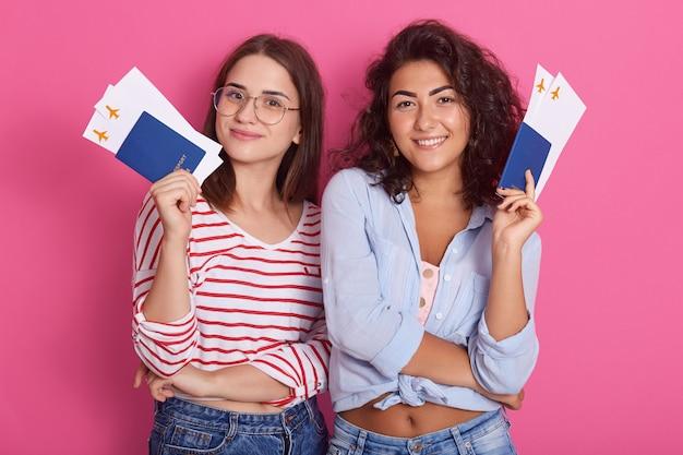 Jonge dolblije vrouwelijke studenten die paspoorten met instapkaartkaartjes houden