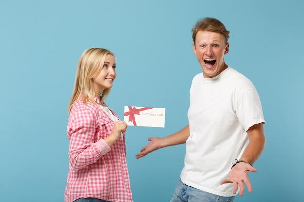 Jonge dolgelukkige paar twee vrienden, man en vrouw in wit roze lege lege t-shirts poseren