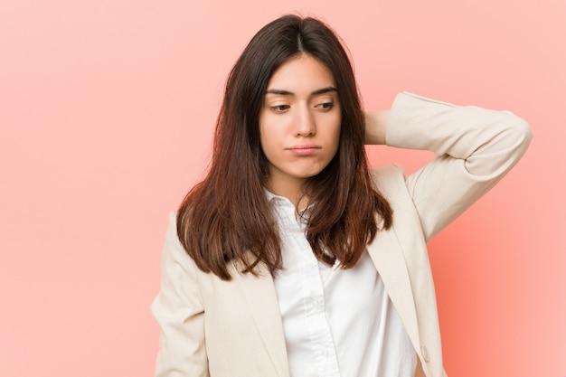 Jonge donkerbruine bedrijfsvrouw tegen een roze achtergrond die hals aan pijn lijdt
