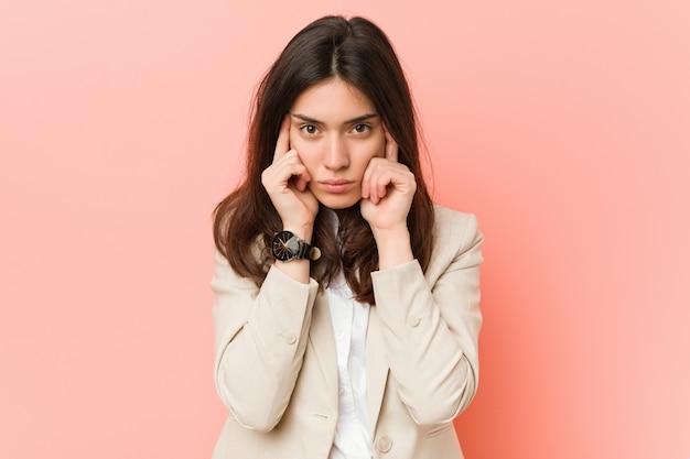 Jonge donkerbruine bedrijfsvrouw tegen een roze muur concentreerde zich op een taak, die wijsvingers hoofd houden.