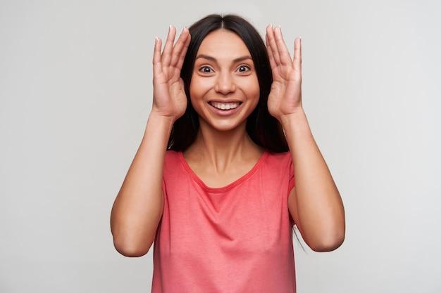 Jonge donkerbruine brunette dame in roze t-shirt met palmen in de buurt van haar gezicht en vrolijk kijkend, in een goede bui terwijl poseren