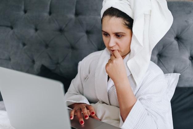 Jonge donkerbruine kaukasische onderneemster die aan haar laptop in haar bed werkt
