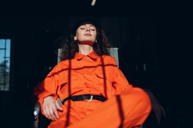Jonge donkerbruine krullende vrouw in oranje kostuum. wijfje in kleurrijk overallportret.