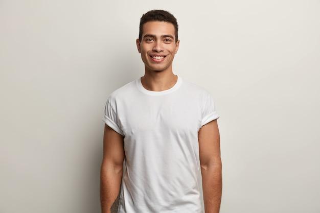 Jonge donkerbruine mens die wit t-shirt draagt