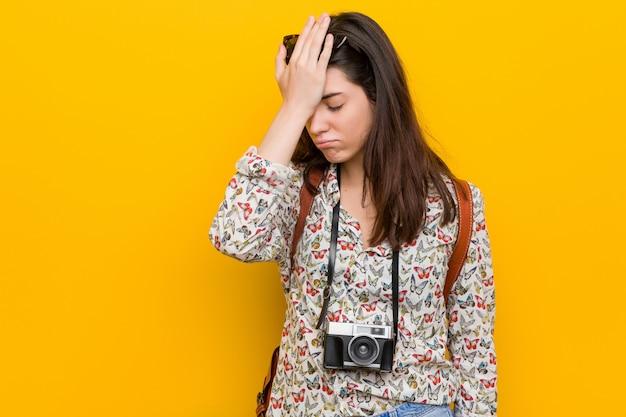 Jonge donkerbruine reizigersvrouw die iets vergeten, voorhoofd met palm meppen en ogen sluiten.