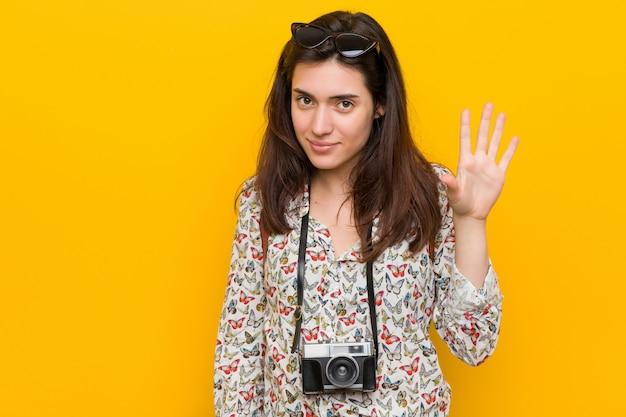 Jonge donkerbruine reizigersvrouw die vrolijk tonend nummer vijf met vingers glimlachen.