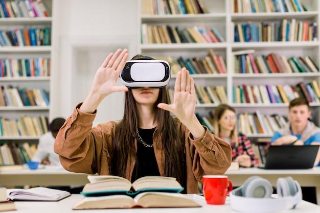 Jonge donkerbruine studente die met vr-simulator in bibliotheek werken. jonge vrouw in vrijetijdskleding en virtuele werkelijkheidsglazen die bij bureau zitten en lucht raken