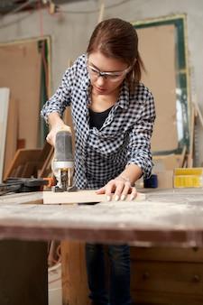 Jonge donkerbruine timmerman die met figuurzaag in workshop werkt